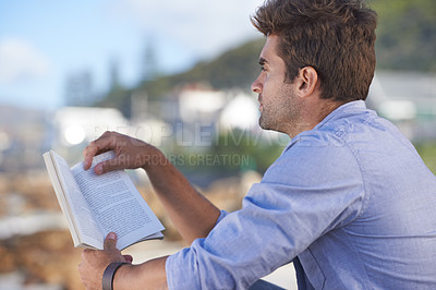Buy stock photo A young man reading a book outdoors