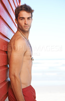 Buy stock photo A handsome young lifeguard standing on the beach
