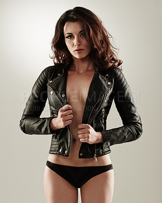 Buy stock photo Portrait of an attractive young woman posing confidently in a leather jacket and panties