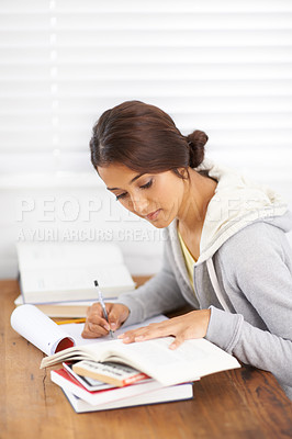 Buy stock photo Side view of a young college student taking notes from her textbook