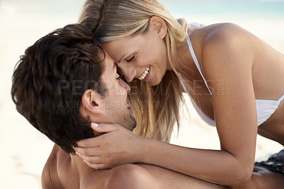 Buy stock photo A happy couple on the beach looking at each other affectionately