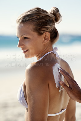 Buy stock photo A beautiful woman on the beach with a person put sunscreen on her back