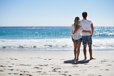 Buy stock photo Back view of a couple with their arms around each other looking at the ocean