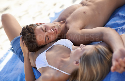 Buy stock photo A young couple relaxing with each other on a towel on the beach