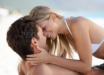Buy stock photo An affectionate young couple kissing at the beach