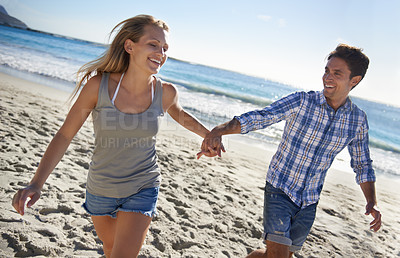 Buy stock photo A young couple walking on the beach