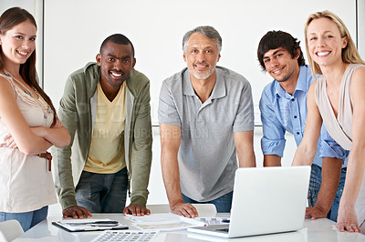 Buy stock photo A group of businesspeople standing behind a desk with a laptop on it smiling at the camera