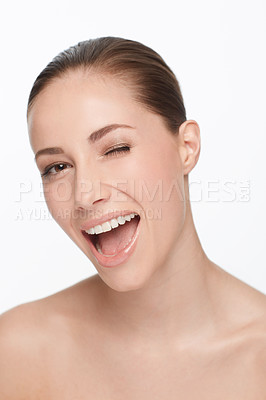 Buy stock photo Cropped view of a nude young woman winking at the camera against a white background