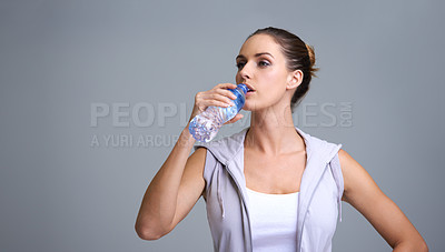 Buy stock photo A beautiful young woman drinking from a water bottle