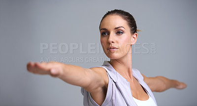 Buy stock photo An attractive young woman exercising in studio