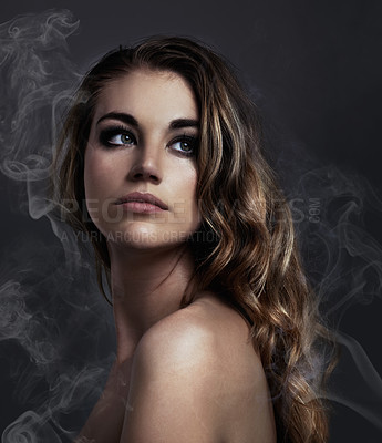 Buy stock photo Studio concept shot of a beautiful young woman with smoke coming off her