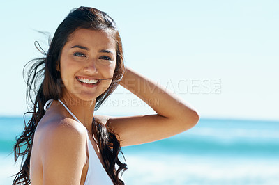 Buy stock photo A gorgeous young woman standing on the beach in the sunshine