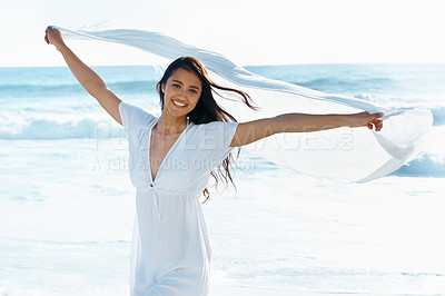 Buy stock photo Beautiful young woman holding up a linen cloth as the wind catches it