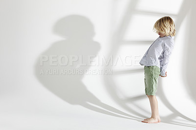 Buy stock photo Studio shot of a young boy standing and looking at his own shadow