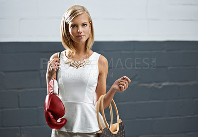 Buy stock photo A beautiful stylish young woman holding a purse in one hand and boxing gloves in the other