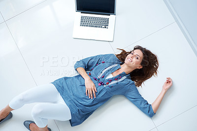 Buy stock photo Happy young woman lying on floor by laptop