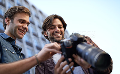 Buy stock photo Low angle shot of two men looking at the lcd screen on a digital camera