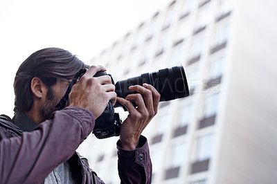 Buy stock photo A young man taking a picture with his camera