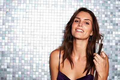 Buy stock photo Portrait of a young woman smiling at the camera while holding up a glass of champagne