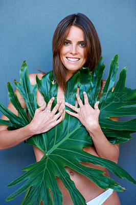 Buy stock photo Sexy young woman covering her breast with leaves