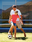 Father and daughter playing a game of soccer