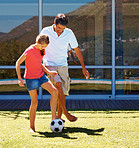 Girl and her dad playing football