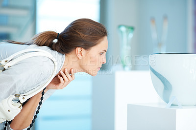 Buy stock photo Pretty young woman looking at crockery in a shop