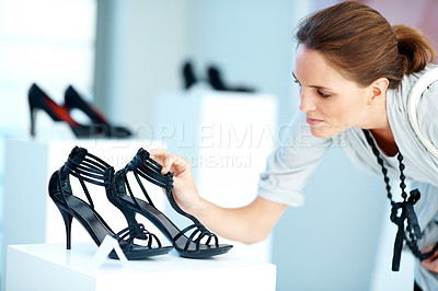 Buy stock photo Pretty young lady choosing shoes at a store