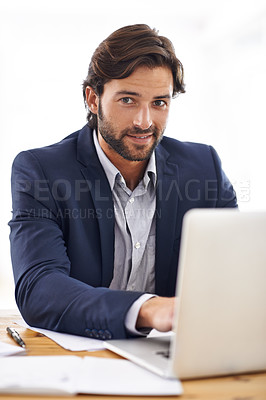 Buy stock photo A portrait of a handsome businessman working on his laptop