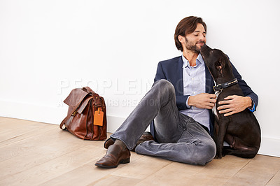Buy stock photo An attractive businessman sitting next to his dog