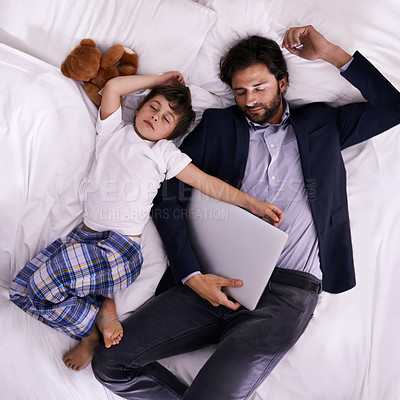 Buy stock photo A father and son sleeping on a bed while his father is still fully dressed and holding a laptop