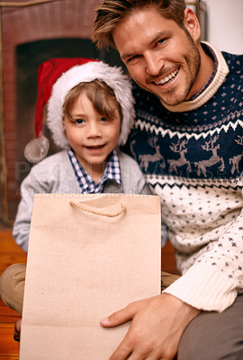 Buy stock photo A boy and his dad sitting with a gift on Christmas eve