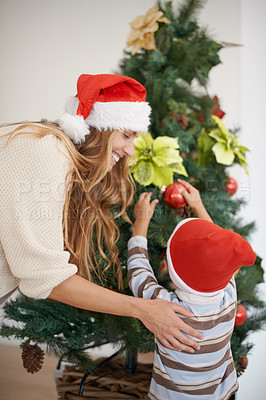 Buy stock photo Shot of a young boy decorating a christmas tree with his mother's help