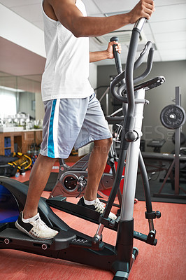 Buy stock photo Shot of a young man exercising on a step climbing machine at the gym
