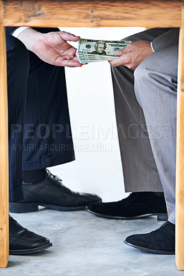 Buy stock photo Cropped shot of money passing hands under a table