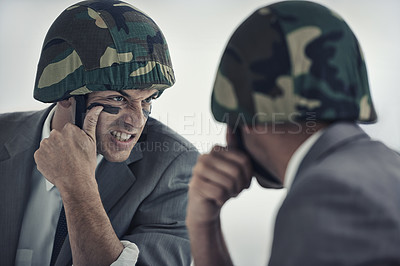 Buy stock photo A young man applying camouflage paint to his face