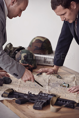 Buy stock photo Two men in suits discussing plans while guns and a map lie on a table