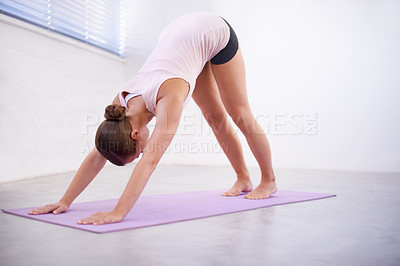 Buy stock photo An attractive young woman in a downward facing dog position