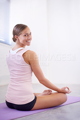 Buy stock photo An image of an attractive young woman in the lotus pose looking over her shoulder