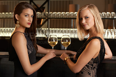 Buy stock photo Shot of two women standing at a bar in evening wear