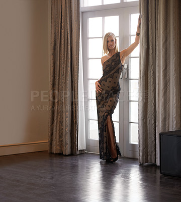 Buy stock photo Full-length portrait of a beautiful young woman leaning against a doorway in an elegant interior