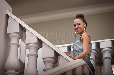 Buy stock photo Portrait of an attractive young woman smiling while standing on a staircase
