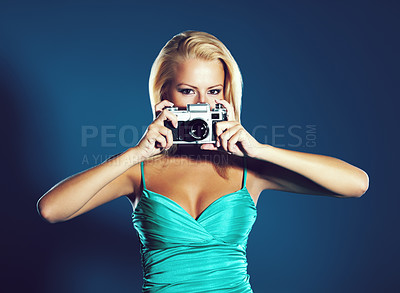 Buy stock photo A pretty young woman holding a camera while isolated on a blue background