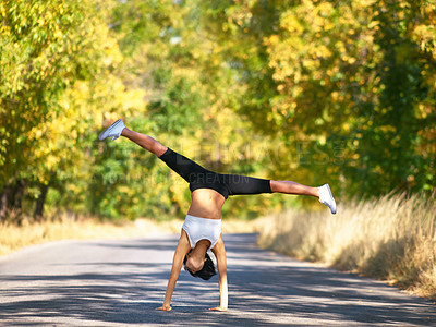 Buy stock photo A young woman doing a cartwheel in the middle of the road