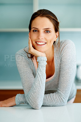 Buy stock photo Smart young woman standing at the kitchen counter