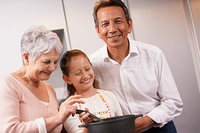 Buy stock photo A young girl being taught how to cook by her grandparents