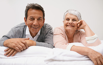 Buy stock photo Portrait of a smiling senior couple relaxing on their bed
