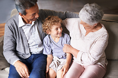 Buy stock photo Grandparents sitting on the couch with their grandson