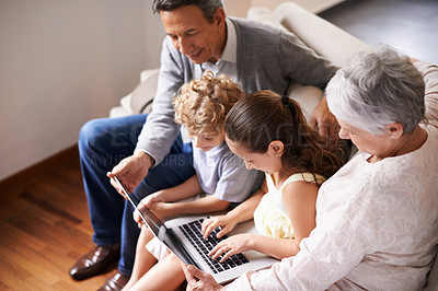 Buy stock photo Group shot of a brother and sister sitting with a laptop and bonding with their grandparents