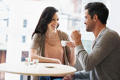 Buy stock photo Shot of a young couple grabbing a cup of coffee together
